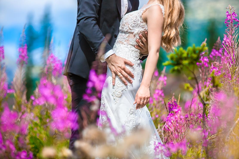fotografia ślubna w naturze - kwiaty Wierzbówki i pan młody obejmujący panią młodą