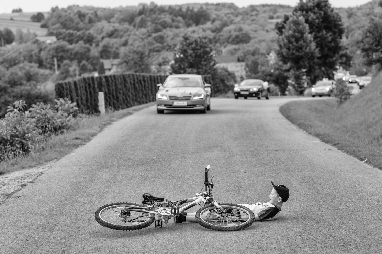 fotografia przedstawiająca chłopca leżącego na drodze po wypadku na rowerze - brama ślubna