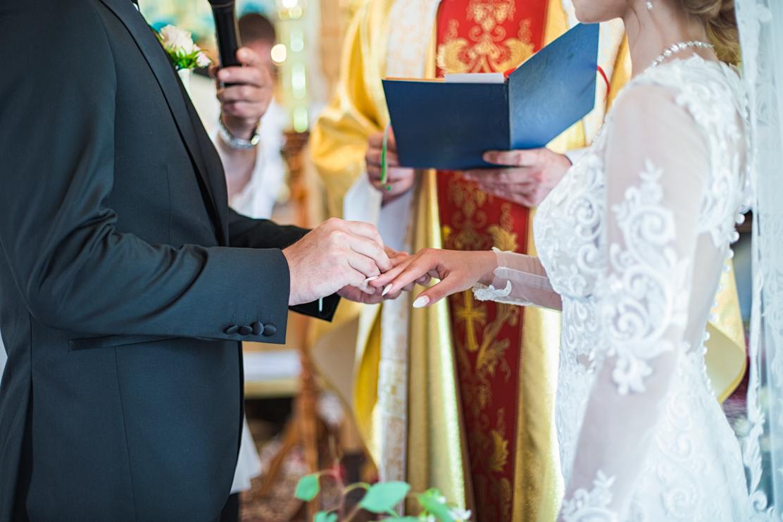 fotografia ślubna przedstawiająca moment zakładania obrączek ślubnych