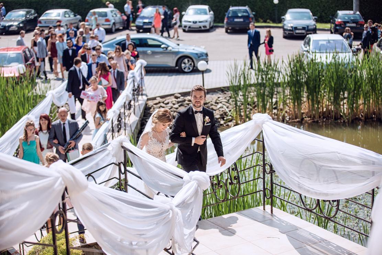 zdjęcie ślubne przedstawiające wejście pary młodej z gośćmi na salę - Jasło
