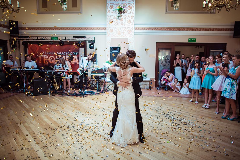 fotografia ślubna pierwszego tańca widziana w szerokim kadrze - wokół pary goście weselni