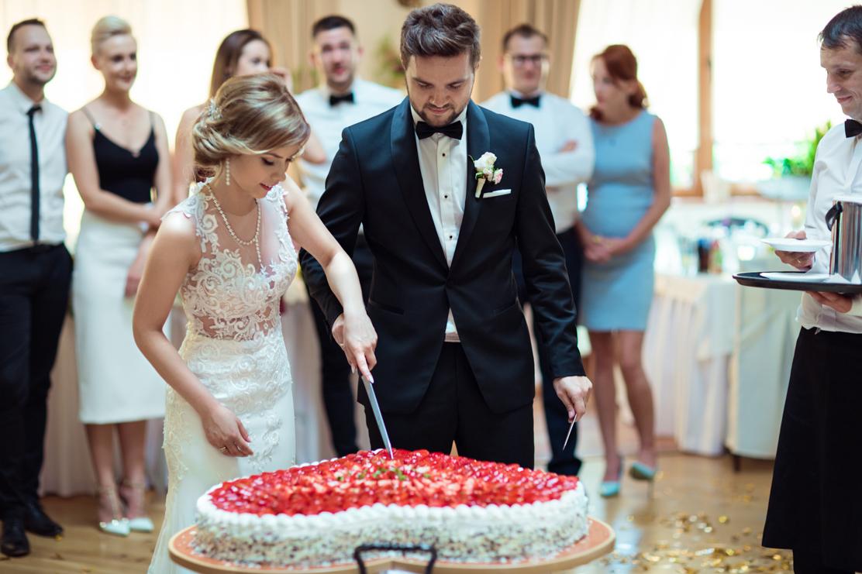 fotografia ślubna na której widać wspólne krojenie tortu weselnego