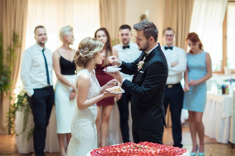 fotografia ślubna przedstawiająca wspólne karmienie się tortem weselnym