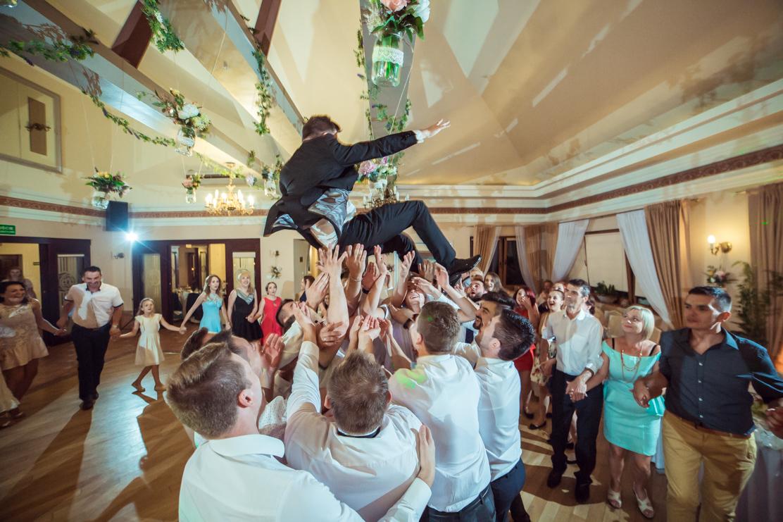 fotografia ślubna przedstawiająca podrzucanie pana młodego przez gości weselnych
