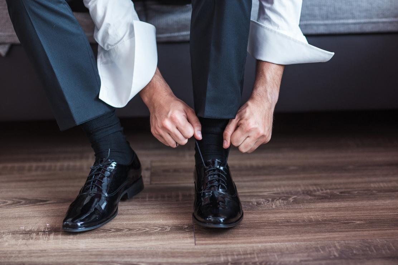 fotografia ślubna z przygotowań pana młodego - wiązanie butów