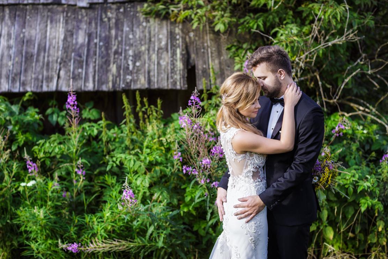 górska sesja ślubna i zdjęcie obejmujących się nowożeńców z pięknymi kwiatami w tle