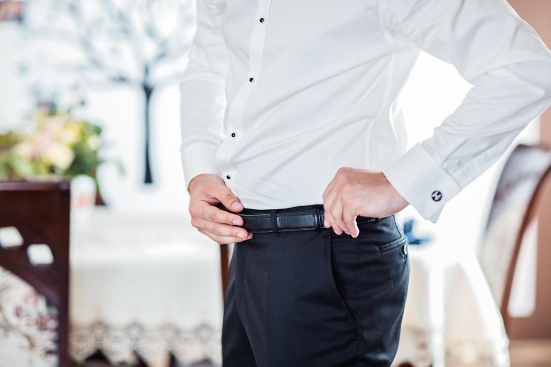 fotografia ślubna z przygotowań pana młodego - ubieranie paska do spodni