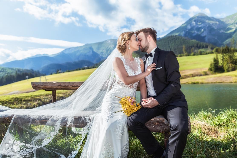 plener ślubny na Słowacji i fotografia ślubna przedstawiająca pare młodą siedzącą na drewnianej ławce