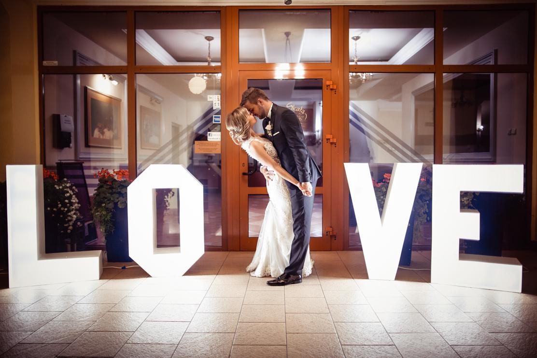 love - fotografia ślubna przed lokalem Zajazd Pod Skałą w świetle napisów