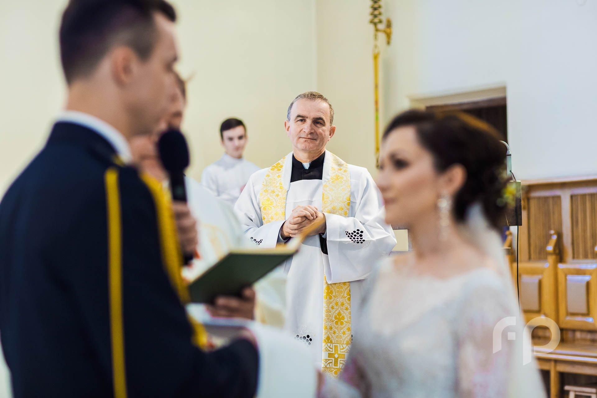 ksiądz obserwujący przysięgę małżeńską