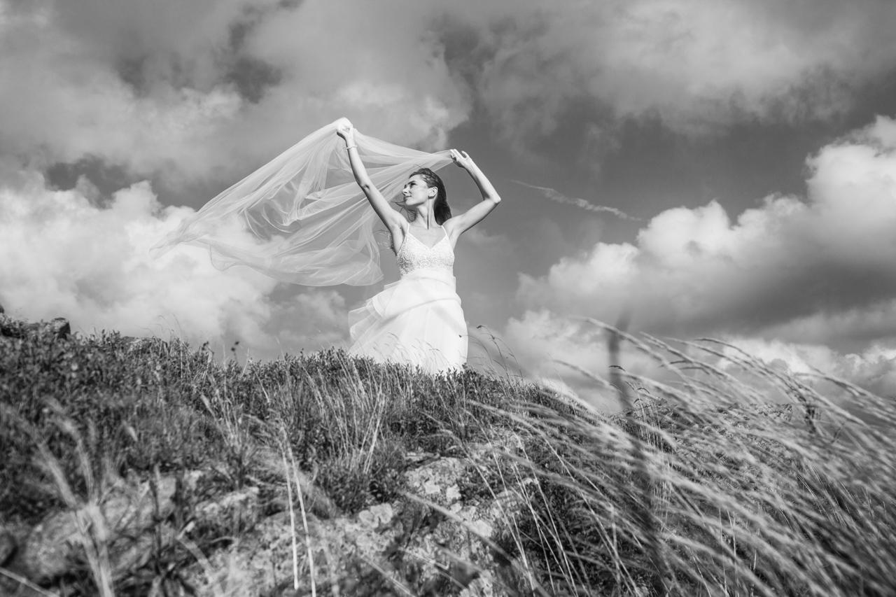 Katarzyna trzymająca welon ślubny podczas porywistego wiatru w Bieszczadach