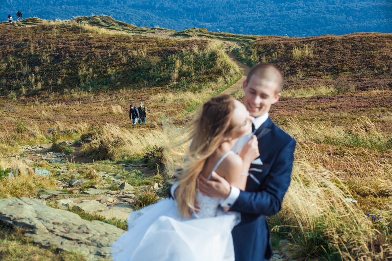 radosne objęcia pary młodej a w tle turyści