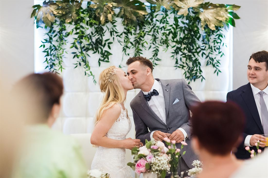 pocałunek pary młodej na sali weselnej